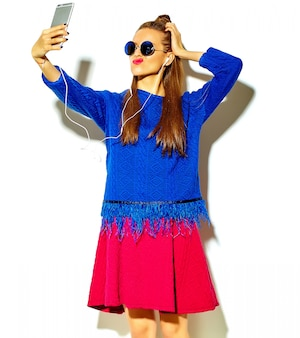 スマートフォンでselfie写真を作る白で隔離される赤い唇とカジュアルな夏のカラフルな服で美しい幸せかわいい笑顔セクシーなブルネットの女性少女
