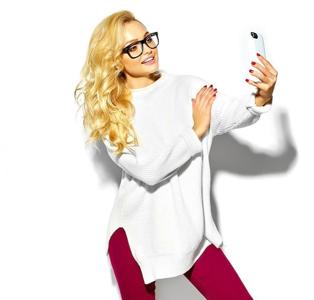 Selfieを取ってメガネでカジュアルなヒップスター暖かい白いセーター服で美しい幸せな甘いかわいい笑顔金髪女性女性