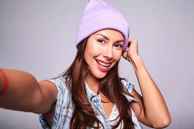 グレーに分離された携帯電話でselfie写真を作る紫色のビーニーでメイクなしのカジュアルな夏ジーンズ服で美しい笑顔かわいいブルネットの女性モデルの肖像画