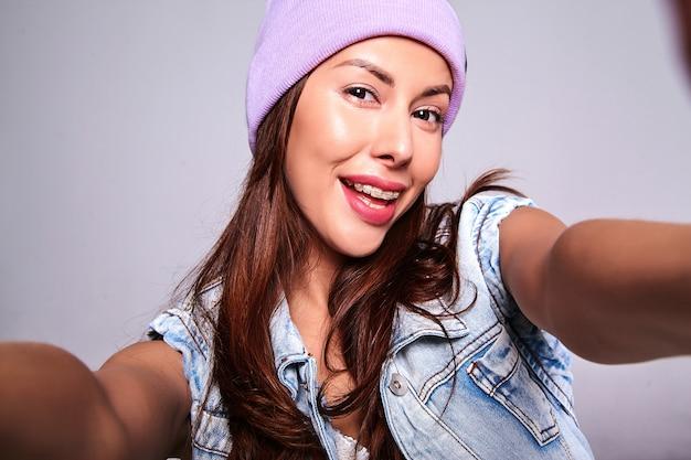 グレーに分離された携帯電話でselfie写真を作る紫色のビーニーでメイクなしのカジュアルな夏のジーンズ服でかわいいブルネット美人モデルの肖像画