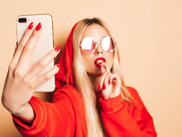 トレンディなジーンズの服と彼女の鼻にイヤリングの若い美しい流行に敏感な悪い女の子の肖像画。セクシーな屈託のない笑顔の金髪女性がselfieを取ります。