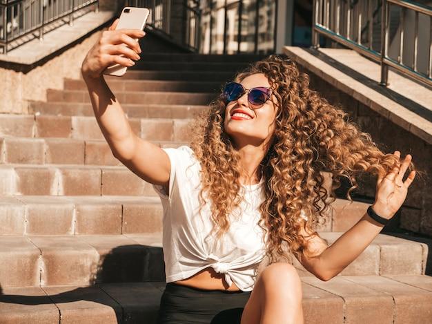 Selfieを取って通りの階段に座っている屈託のない少女