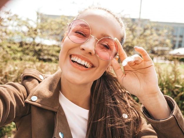 夏の流行に敏感なジャケットで美しい笑顔ブルネットの少女のクローズアップの肖像画モデルは、スマートフォンでselfieを取ってモデルサングラスの通りの暖かい晴れた日に写真を作る女性