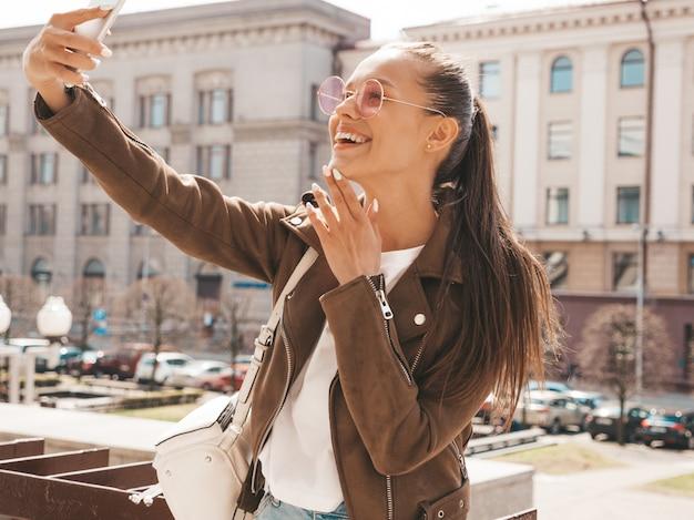 夏の流行に敏感なジャケットで美しい笑顔ブルネットの少女の肖像画。スマートフォンでモデル撮影selfie。