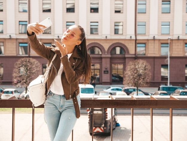 夏の流行に敏感なジャケットとジーンズの若い美しい笑みを浮かべて少女の肖像画。スマートフォンでselfieを撮るモデル。通りで写真を作る女性。サングラス。空気キスを与える