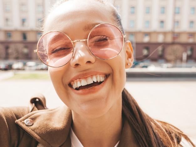夏の流行に敏感なジャケットで美しい笑顔ブルネットの少女のクローズアップの肖像画。スマートフォンでモデル撮影selfie。