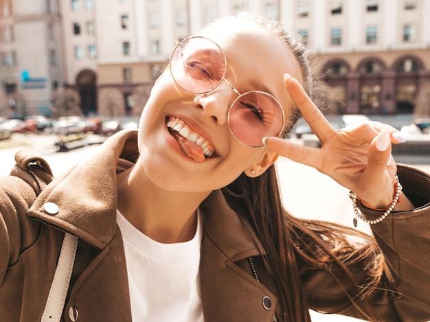 夏の流行に敏感なジャケットの美しい笑顔ブルネットの少女。スマートフォンでモデル撮影selfie。