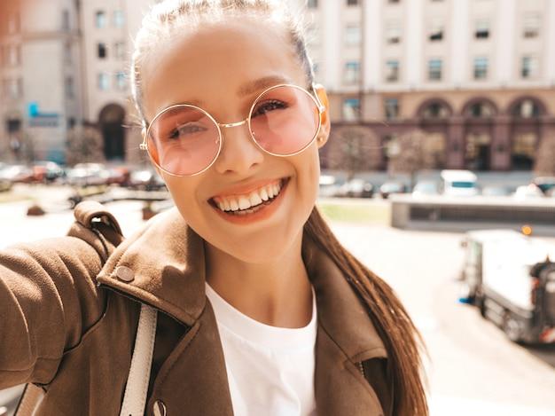 夏の流行に敏感なジャケットとジーンズの美しい笑顔少女の肖像画。スマートフォンでselfieを取ってモデル。