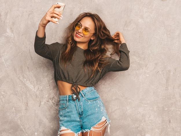 インスピレーションと写真selfieを取り、モダンな服を着て陽気な若い女性の肖像画。スマートフォンのカメラを保持している女の子。モデルのポーズ