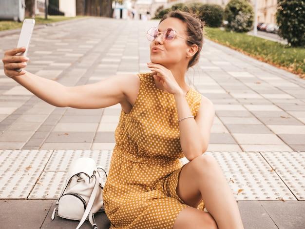 夏の流行に敏感な黄色のドレスで美しい笑顔ブルネットの少女のクローズアップの肖像画。スマートフォンでselfieを撮るモデル。サングラスの通りの暖かい晴れた日に写真を作る女性