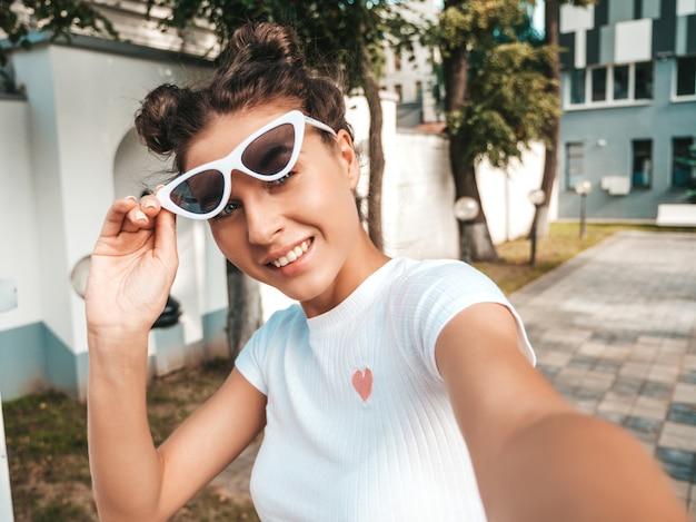 夏のカジュアルな服に身を包んだ角髪型の美しい笑顔モデル。サングラスで通りでポーズをとってセクシーな屈託のない少女。スマートフォンでselfieのセルフポートレート写真を撮る