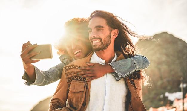 ソーシャルネットワークストーリー-新しいトレンドテクノロジーを楽しんでいるインフルエンサーの人々-愛、ライフスタイル、および多民族関係の概念-男の顔に主な焦点を当ててselfie写真を撮る幸せなカップル