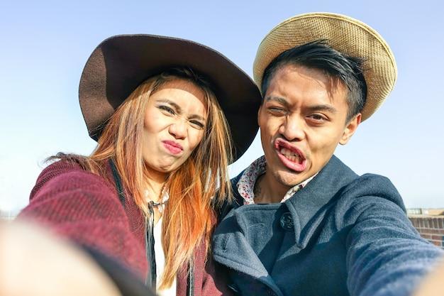 面白い顔でselfieを作る流行に敏感なアジアカップル