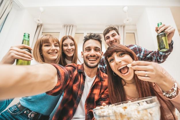 Счастливые люди, принимая selfie дома вечеринку. лучшие друзья веселятся в помещении и пьют пиво. встречайте людей, путешествующих концепции