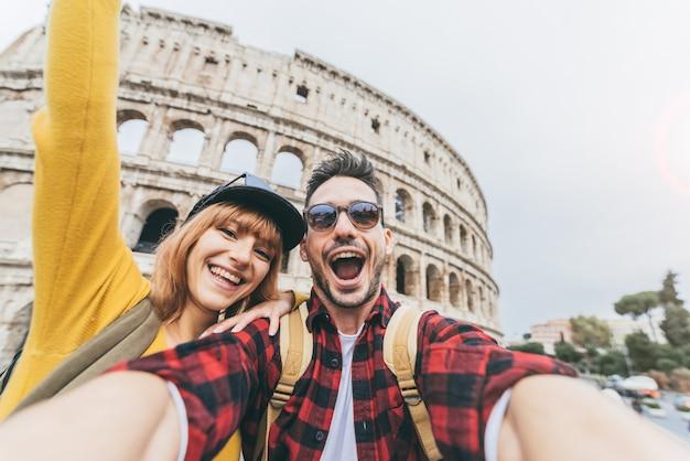 ローマのコロッセオの前でselfieを取って楽しんで観光客の幸せなカップル。人々はイタリアのローマを旅行します。