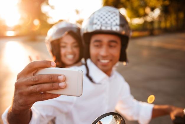 幸せなアフリカのカップルは屋外で現代のバイクに乗って、スマートフォンでselfieを作ります。電話に集中