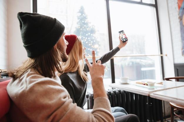 Selfieを作るカップルの後ろからの眺め