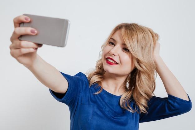 魅力的な若い女性は電話でselfieを作る