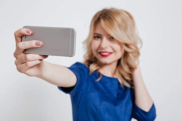 ゴージャスな若い女性が電話でselfieを作る