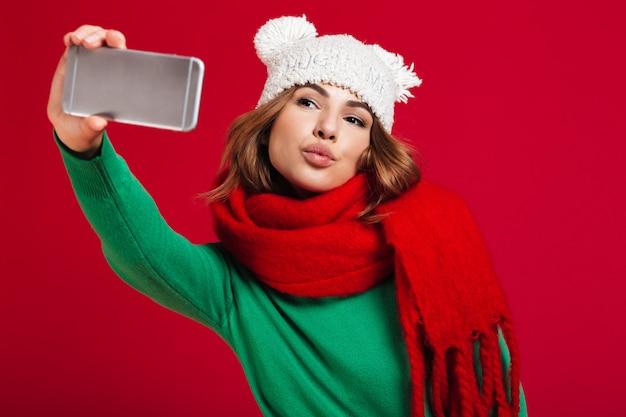 美しい若い女性はキスを吹いて電話でselfieを作ります。