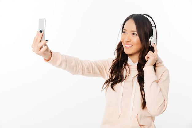 アジアの陽気な女性が音楽を聴くと、携帯電話でselfieを作ります。