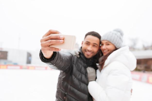 アイススケートリンクでスケートをしている陽気なカップルは、電話でselfieを作ります。