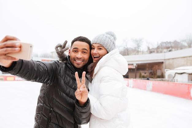 笑顔の愛情のあるカップルは、電話と平和のジェスチャーでselfieを作ります。