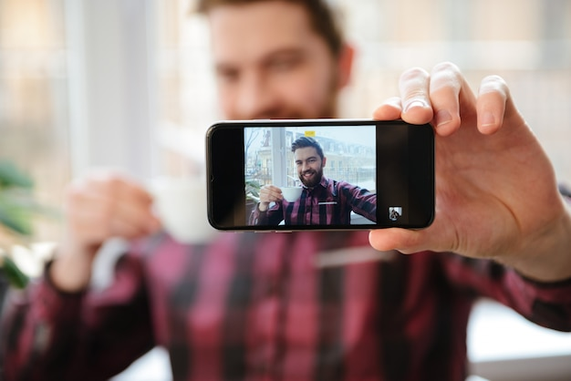 ひげを生やした若い男が携帯電話でselfieを作る
