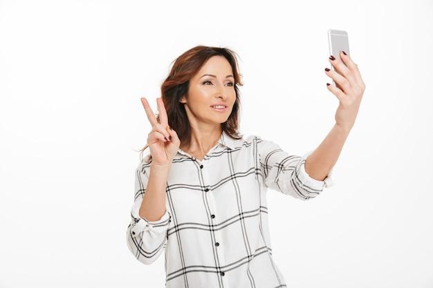 携帯電話でselfieを取り、勝利のサインを示す陽気な大人の女性、スタジオで白い背景に分離