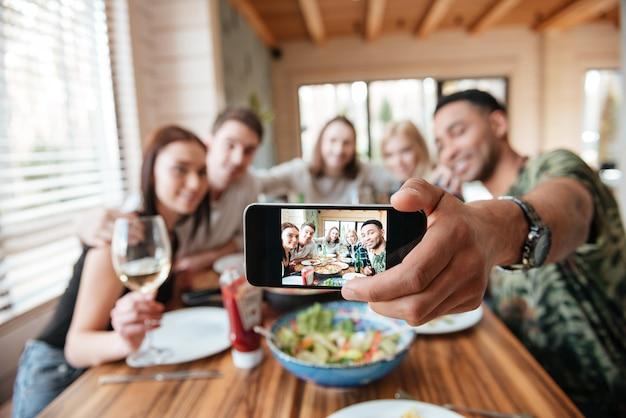 夕食を食べて、スマートフォンでselfieを取っている友人のグループ