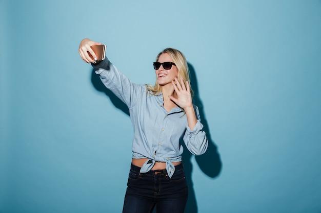 シャツとサングラスのスマートフォンでselfieを作る幸せな女
