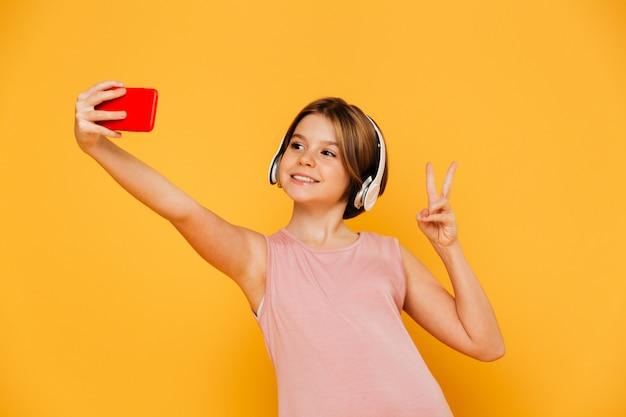 分離されたスマートフォンでselfieを作るかなりモダンな女の子