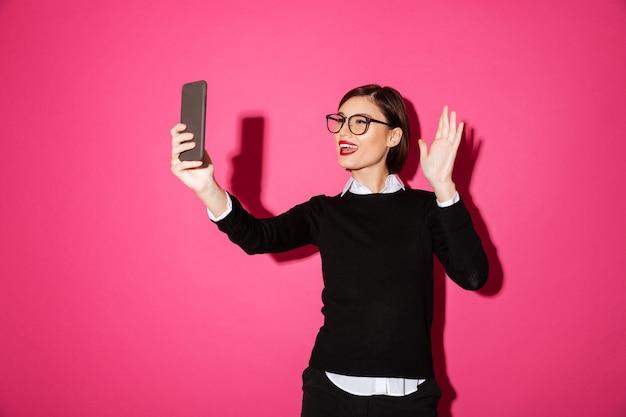 分離されたスマートフォンでselfieを作る若い女性