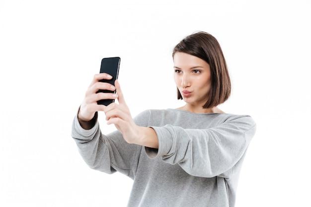 携帯電話でselfieを取ってかなり若い女性