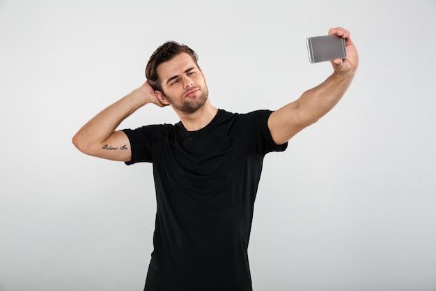 深刻なスポーツマンは携帯電話でselfieを作る