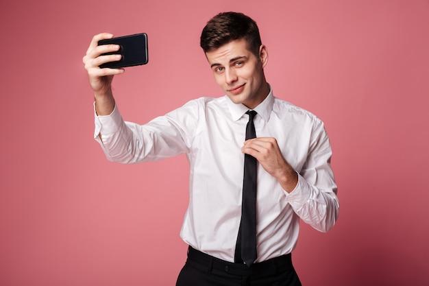 Красивый молодой бизнесмен сделать selfie по мобильному телефону.