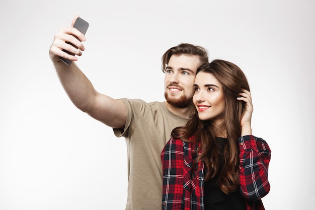 Славная жизнерадостная пара принимая selfie на телефоне, смотрящ счастливый