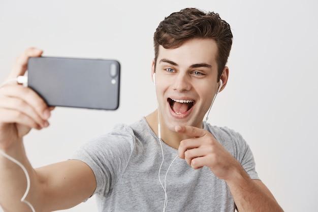 携帯電話を持って、selfieのポーズをとって、ビデオ通話をして、広く笑って、携帯電話の画面で人差し指で指している見栄えの良いヨーロッパ人。現代のコミュニケーションとテクノロジー。