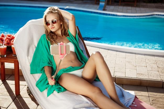 笑みを浮かべて、selfieを作って、スイミングプールのそばに横たわって美しいブロンドの女性