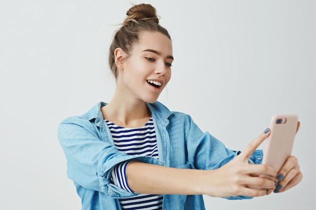 女性の角度を見つけることは、素晴らしいインターネットのオンライン投稿を撮ります。魅力的なスタイリッシュなファッショナブルな女性が真新しいスマートフォンを持っている手を伸ばしてselfieを作る