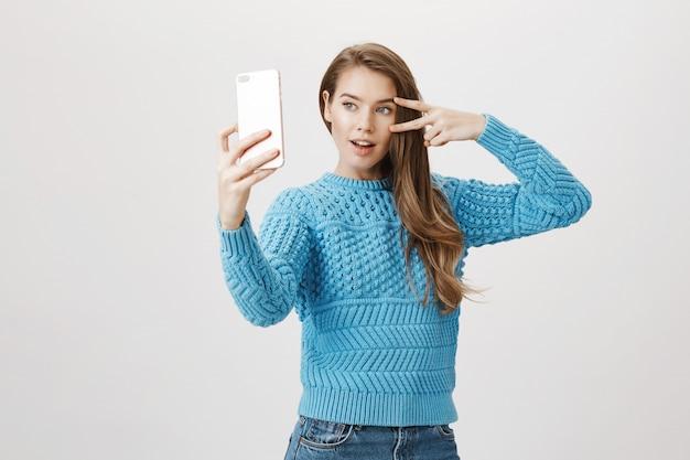 スマートフォンでselfieを取ってグラマースタイリッシュな女性