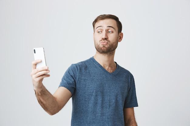 愚かなハンサムな男がスマートフォンでselfieを取って、ふくれっ面