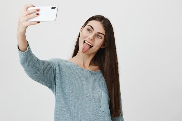 Selfieを取って、舌を見せて笑っているスタイリッシュな魅力的な女性
