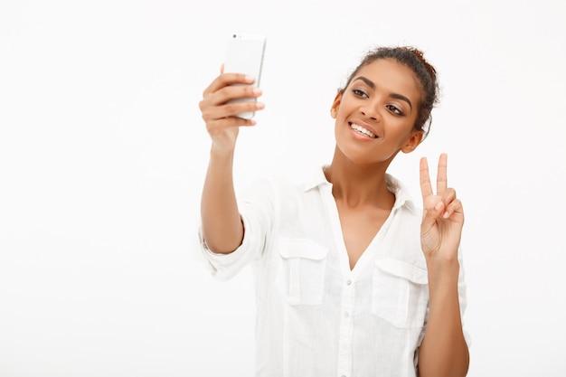Портрет молодой африканской женщины делая selfie на белизне
