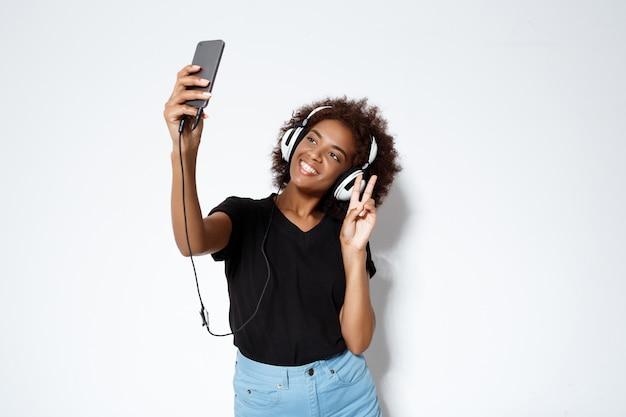 Красивая африканская девушка в наушниках делая selfie над белой стеной.