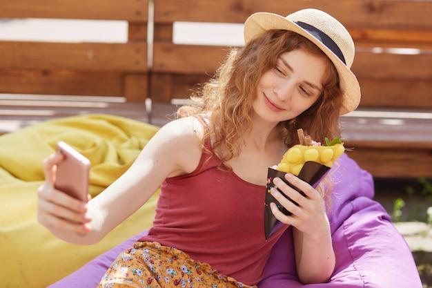 Selfieを取って、片手でスマートフォンを保持している、食べ物を持っている、カラフルなビーンズバッグに座って、外の木製のフェンスを越えてポーズ笑顔のリラックスした若い女の子の肖像画を閉じます。残り時間の概念。