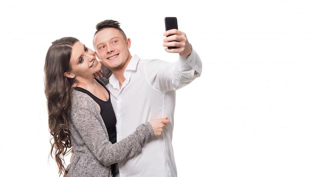 Время селфи. красивые молодые пары обнимая и усмехаясь пока делающ selfie, стоя над стеной изолированной белизной.