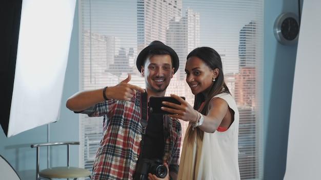 プロのスタジオ写真撮影でハンサムなカメラマンとselfieを作る美しいアフリカモデル