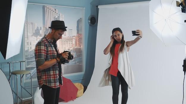モダンなスタジオでの写真撮影中にスマートフォンでselfieを作るかなり黒いモデル