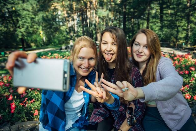 夏の公園でスマートフォンでselfieを取ってかわいいガールフレンドの肖像画